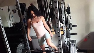Sportive babe Tia lifting weight at the home gym