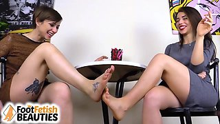 Two sexy barefoot brunettes play footsies under the table