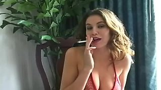 Big breasted brunette smokes a cigarette in red lingerie