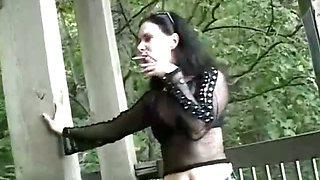 Brunette slut wearing fishnet shirt smoking sexy at the